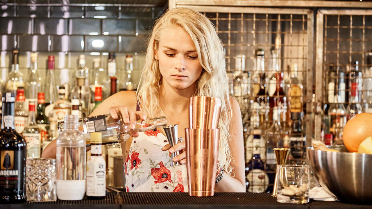 blonde beartender preparing a cocktail