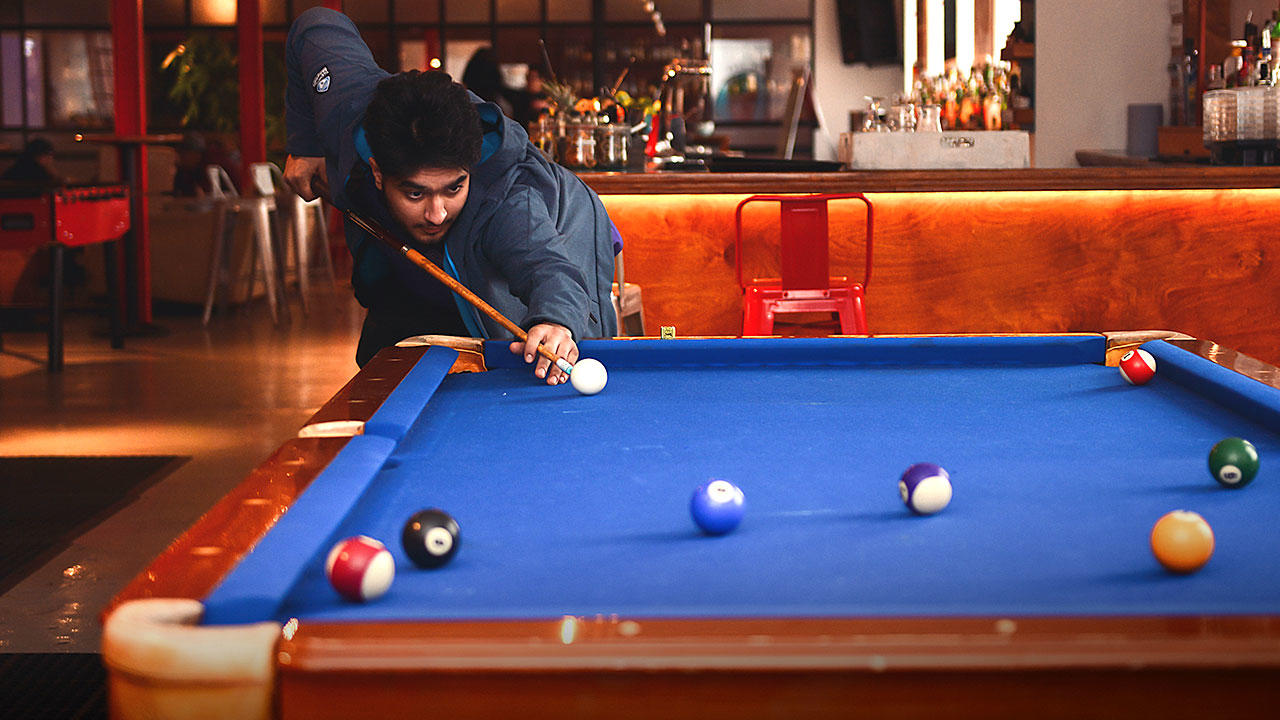 Student playing billiards during break from barman course