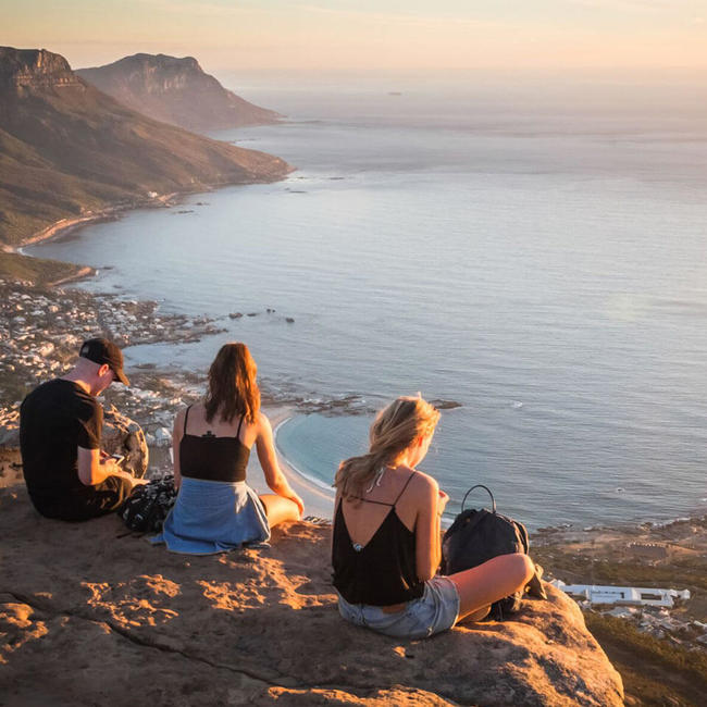 three young adults sitting on cliff watching sunset in cape town