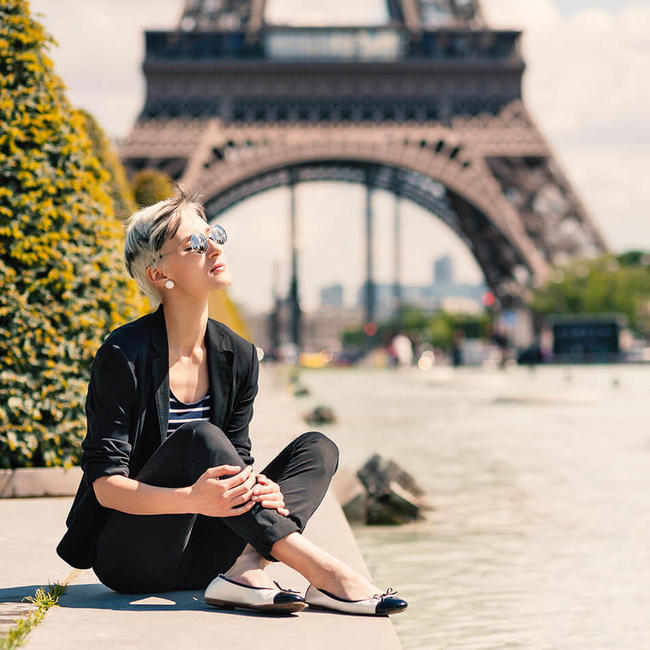 parisian young woman sitting in front of unfocussed background of eiffel tower