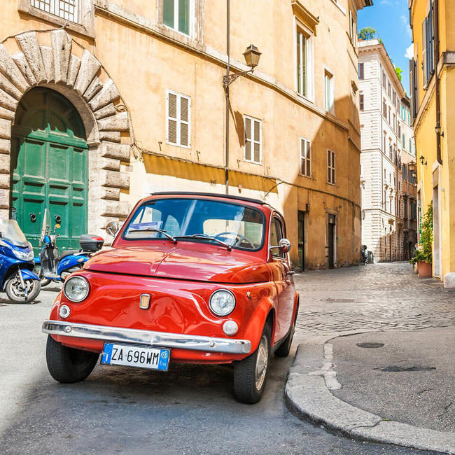red classic car parked in a picturesque street in rome