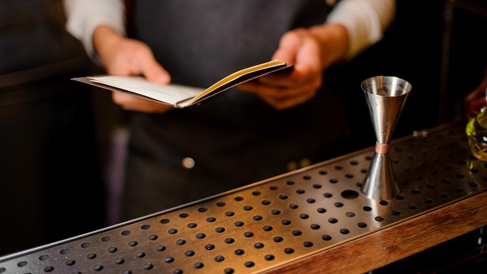 bartender reading cocktail recipe book